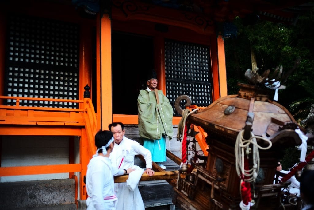 Shinto priest is thanking all men for working so hard to carry of miniature shrines